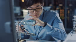 Close Up of a Professional Japanese Electronics Development Engineer in Blue Shirt Soldering a Circuit Board in a High Tech Research Laboratory with Modern Computer Equipment.