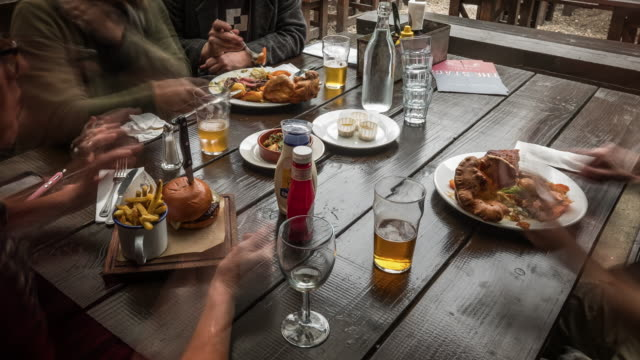close up of a pud garden table as friends enjoy a drink and traditional sunday roast - pub stock videos & royalty-free footage