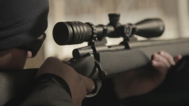 Close up of a rifle stock, scope and trigger as a man takes aim and fires, shoots the bullet.