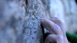 Close up of a rock climber's fingers and boot on the rock as he starts to climb a new route