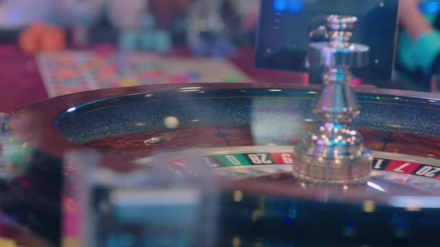 slo mo. cu. close up of a roulette ball spinning around a roulette wheel in a casino in las vegas while wedding party waits to see if they have won - casino stock-videos und b-roll-filmmaterial