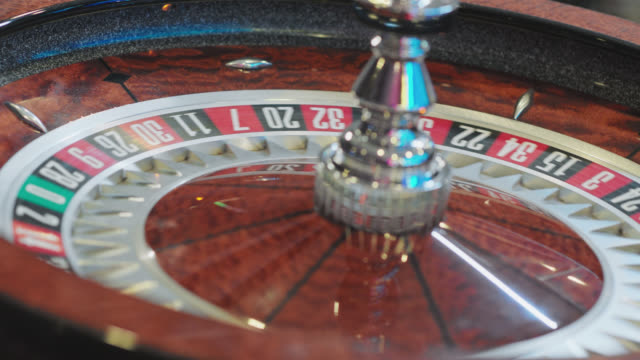 slo mo. cu. close up of a roulette ball spinning around a roulette wheel in a casino in las vegas. - roulette stock videos & royalty-free footage