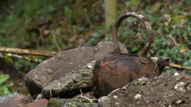 close up of a rusty kettle by concrete chips - beccuccio video stock e b–roll