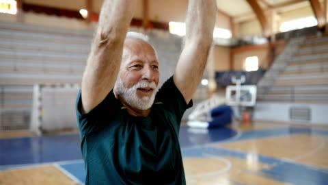 närbild av en senior man gör övning på aerobisk klass - aktiva pensionärer bildbanksvideor och videomaterial från bakom kulisserna