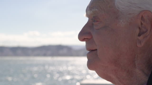 Close up of a senior man looking ahead with the out of focus sea behind him
