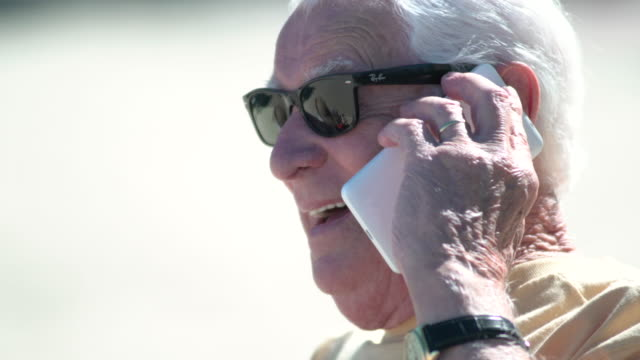 close up of a senior man talking to the phone at the beach - senior men stock videos & royalty-free footage