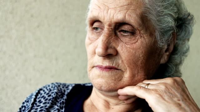 vidéos et rushes de pan de gros plan d'une femme senior, perdue dans ses pensées - main au menton