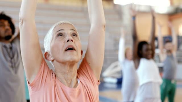 vídeos y material grabado en eventos de stock de cerca de una mujer mayor que se estira después de la clase de baile - delgado