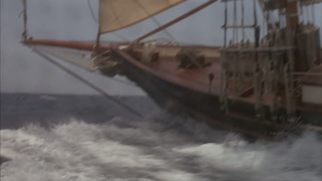Close up of a ship's bow as it crashes through the rough ocean waves.