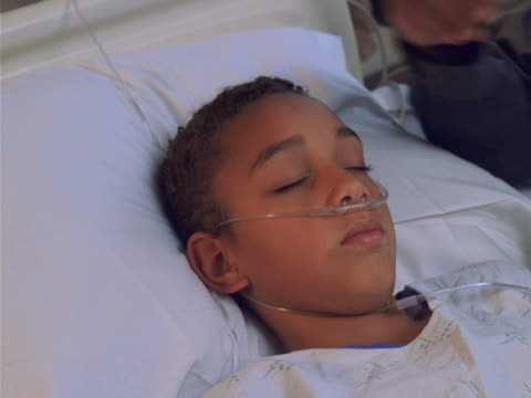 close up of a sleeping boy in his hospital bed being comforted by a loved one - genderblend video stock e b–roll