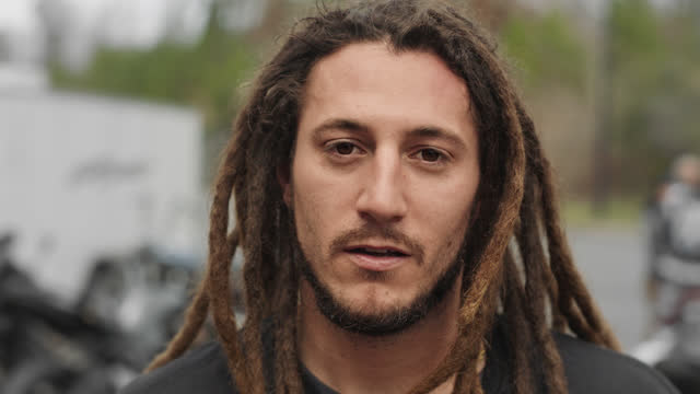 slo mo. cu. close up of a stunt motorcycle rider with brown dreadlocks looking straight into the camera with a serious expression - showing off stock videos & royalty-free footage