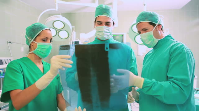 Close up of a surgical team analysing a Xray