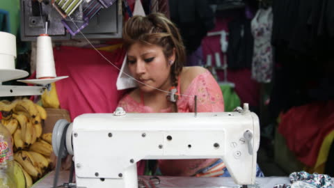 stockvideo's en b-roll-footage met close up of a tailor at work using her sewing machine on a market in piura, peru. - rubriekadvertentie