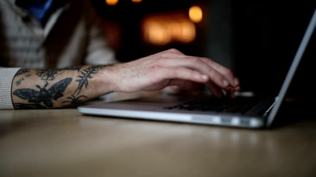 close up of a tattooed man typing on a computer - generazione y video stock e b–roll