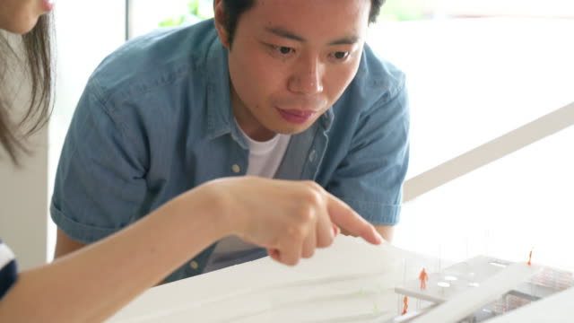Närbild av ett team av arkitekter som inspekterar en 3D arkitektonisk modell