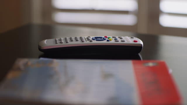 close up of a television remote control on a coffee table. - coffee table stock videos & royalty-free footage