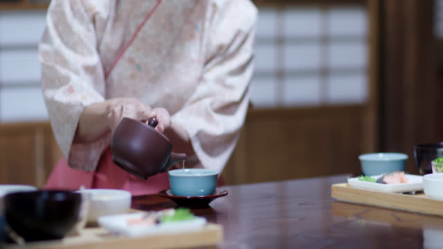 Close up of a traditional Japanese Ryokan owner pouring tea for tourists