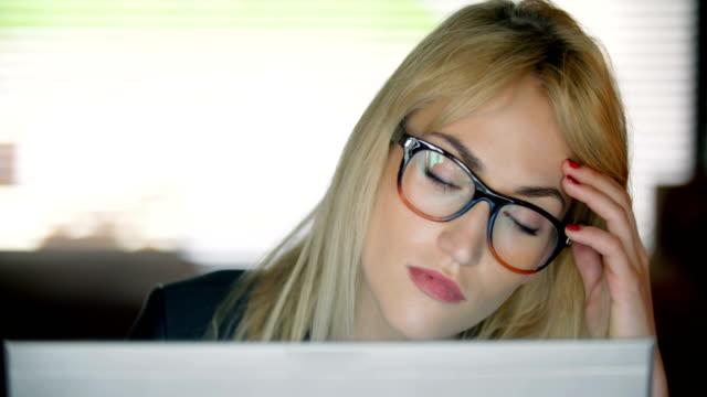 Nahaufnahme einer sehr müde jungen Frau, die bis spät in die Nacht an einem Computer arbeiten.