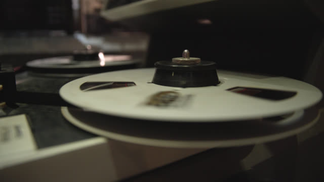 close up of a vintage reel to reel audio machine rotating - 思い出点の映像素材/bロール