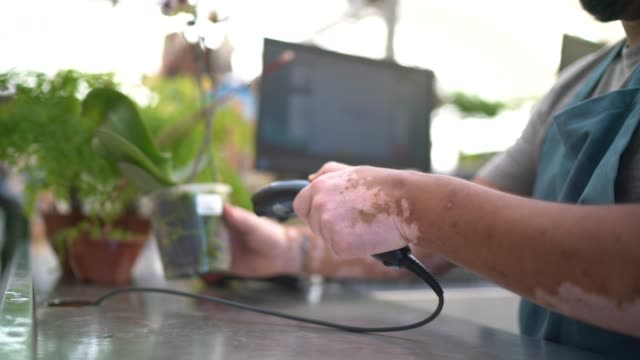 close up of a vitiligo cashier hands using bar code reader in a product - no make up stock videos & royalty-free footage