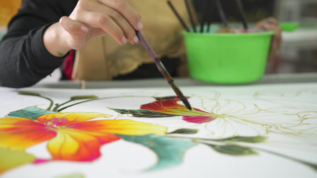 close up of a woman colouring a flower design on batik - batik stock videos and b-roll footage
