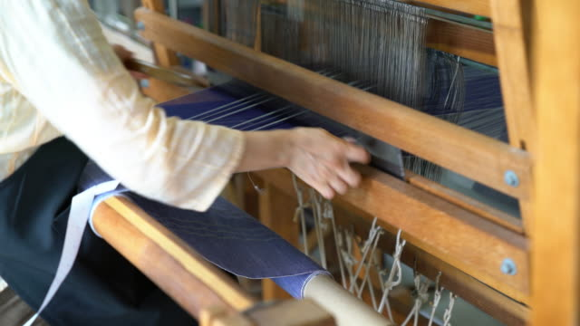 close up of a woman hand weaving fabric, passing the shuttle back and forth - loom stock videos & royalty-free footage