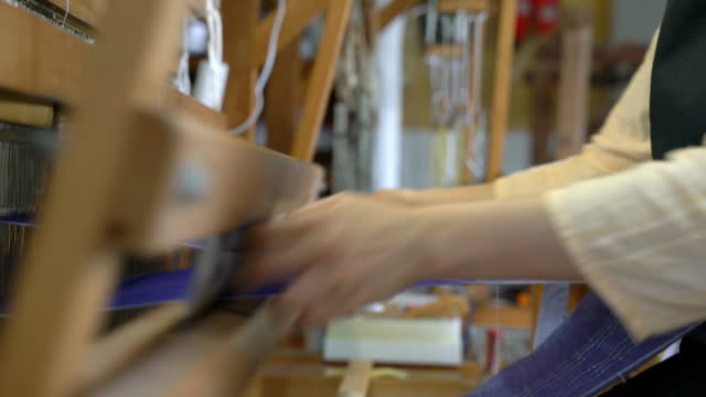 close up of a woman hand weaving fabric, passing the shuttle back and forth - tradition stock videos & royalty-free footage
