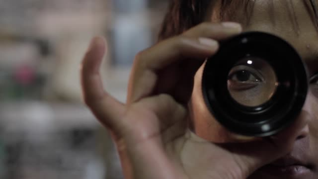 close up of a woman looking through a photo lens - see through stock videos & royalty-free footage