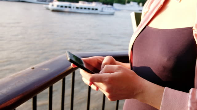 close up of a woman texting on her cellphone along the thames river in london, england at sunset. - naga river stock videos and b-roll footage