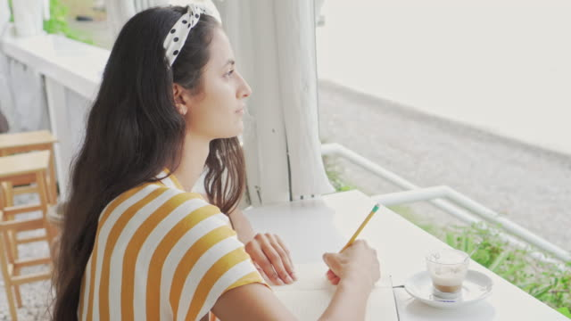 close up of a woman writing by the sea. - pen stock videos and b-roll footage