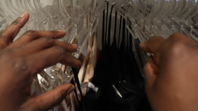 close up of a woman's hands looking through clothes rack - coathanger stock videos & royalty-free footage