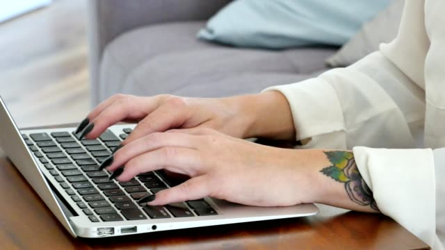Close up of a woman's hands using a laptop