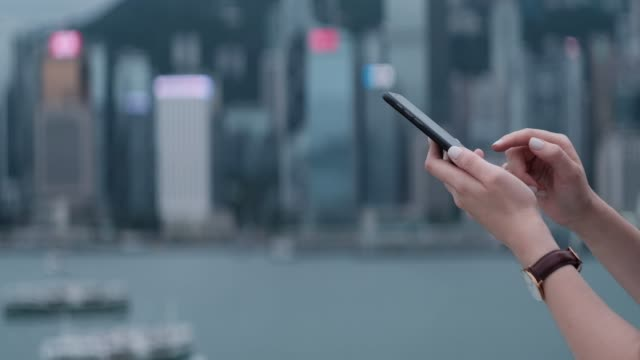 close up of a young asian woman using smartphone in the promenade of victoria harbour, against hong kong city skyline during the day - opportunity stock videos & royalty-free footage
