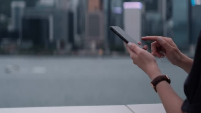 close up of a young asian woman using smartphone in the promenade of victoria harbour, against hong kong city skyline during the day. shifting focus gradually from background to foreground - star ferry stock videos & royalty-free footage