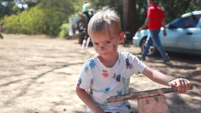 close up of a young boy with dirt on his face sitting on wooden bike while a man walks behind him towards a woman that is loading a dirt bike on the back of a pickup truck - kelly mason videos stock-videos und b-roll-filmmaterial