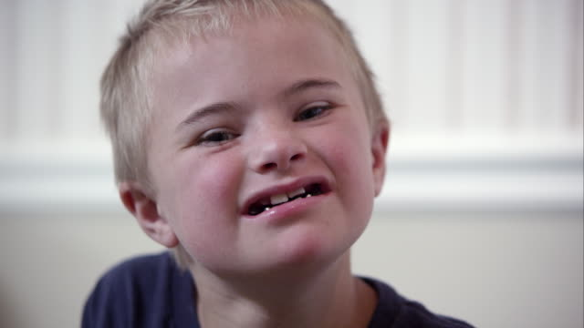 Close up of a young downs syndrome boy's face