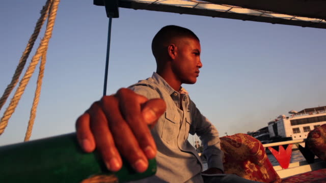 close up of a young egyptian man's hand as he steers a boat - ägypten stock-videos und b-roll-filmmaterial