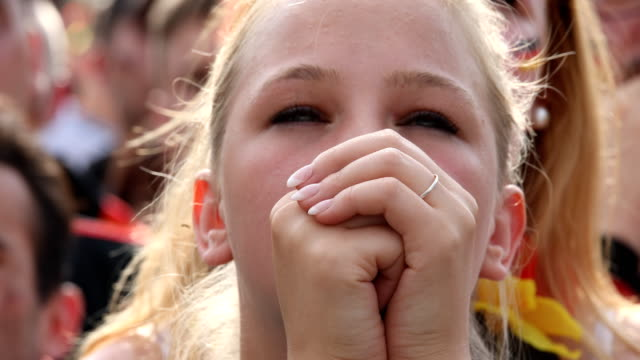 Close up of a young female football fan in a football shirt who is holding her hands in front of her face and who has no hope anymore while Germany...