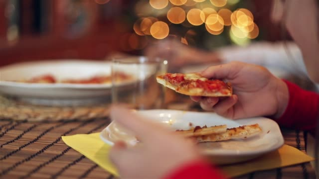 close up of a young girl eating a slice of pizza - parte de una serie video stock e b–roll
