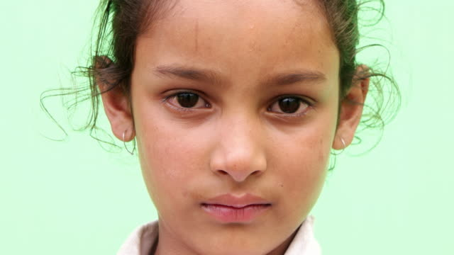 vidéos et rushes de close up of a young girl serious and replying to a question - une seule petite fille