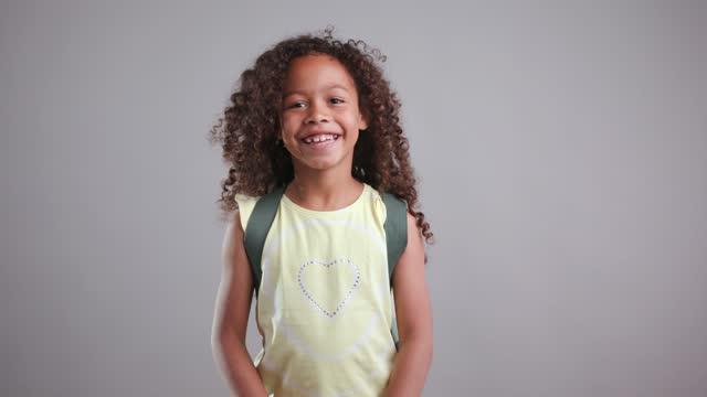カメラを見てバックパックを持つ若い女の子のクローズアップ - 女児1人点の映像素材/bロール