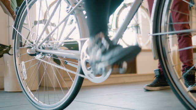 close up of a young hispanic woman's feet as she tries out a new bicycle - partire bildbanksvideor och videomaterial från bakom kulisserna