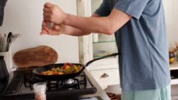 Close up of a young man adding seasoning to a stir fry