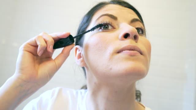 Close up of a young woman applying mascara.