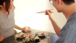 Close up of a young woman showing her boyfriend how to properly use chopsticks
