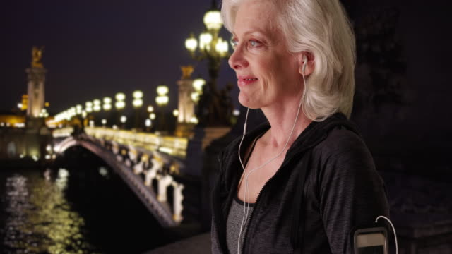 stockvideo's en b-roll-footage met close up of active senior woman working out on paris vacation at night - jogster