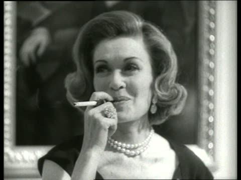 vídeos y material grabado en eventos de stock de b/w close up of actress constance bennett smoking cigarette / 1960's / sound - boquilla producto relacionado con el tabaco