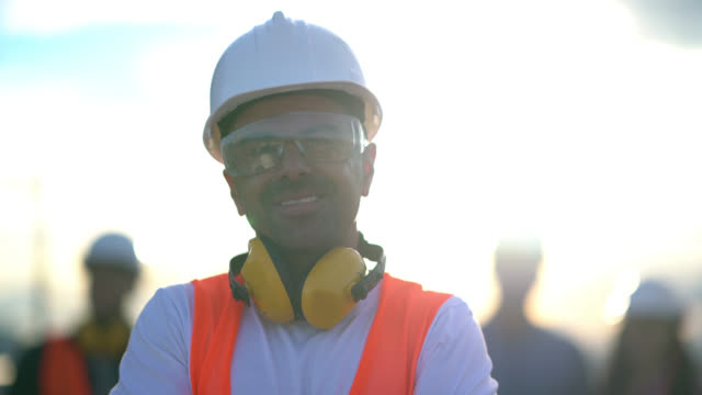vídeos de stock e filmes b-roll de close up of adult construction worker wearing protective goggles and safety helmet looking at camera smiling - óculos de proteção
