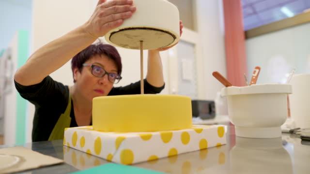 nahaufnahme der erwachsenen frau, die eine schicht kuchen - hot desking arbeitsplatz stock-videos und b-roll-filmmaterial