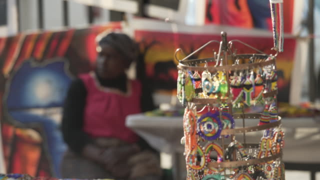 close up of african beads being sold by a female street vendor with some arts and crafts in the background in johannesburgsouth africa - market trader stock videos & royalty-free footage
